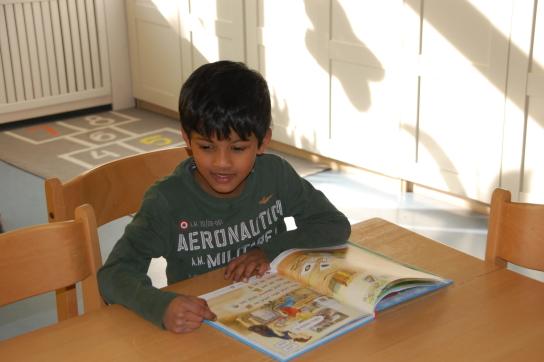 Ein Junge an einem Tisch liest in einem Buch