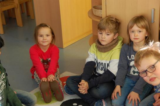 Eine Gruppe von Kindern auf einem Teppich, ein Mädchen guckt direkt zum Betrachter