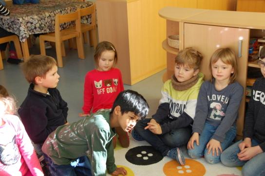 Jungen und Mädchen sitzen in einem Kreis auf einem bunten Teppich