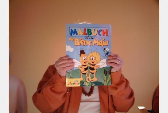Eine Bewohnerin hält ein Biene Maja Malbuch vor ihrem Gesicht.