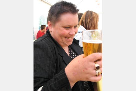 Eine Bewohnerin auf dem Oktoberfest mit einem schönen Glas Bier in der Hand.