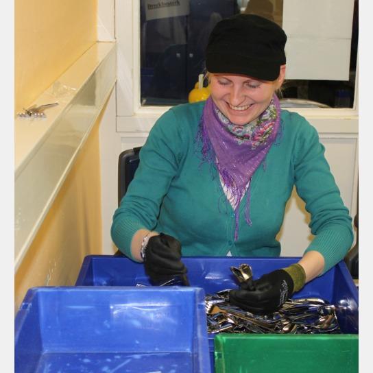 Eine lachende Camfil-Mitarbeiterin beim Sortieren von Besteckteilen.