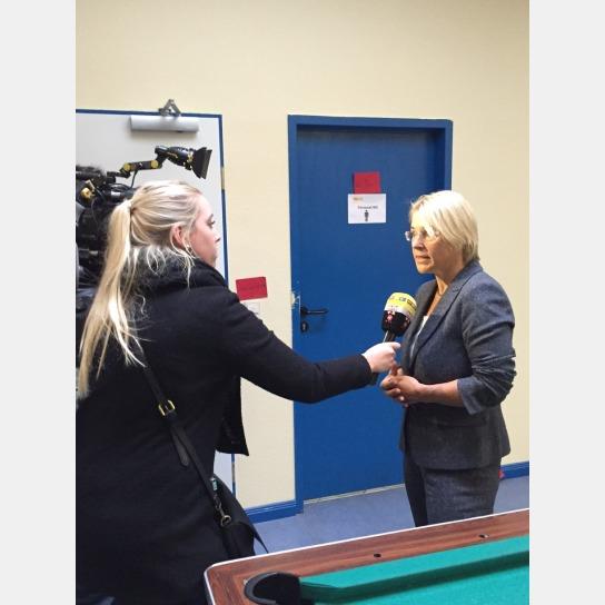 Ein Kameramann und eine junge Frau mit Mikrofon interviewen Sozialministerin Alheit.