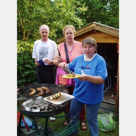 Bewohner und Betreuer gemeinsam beim Sonnerfest mit einer Grillwurst.