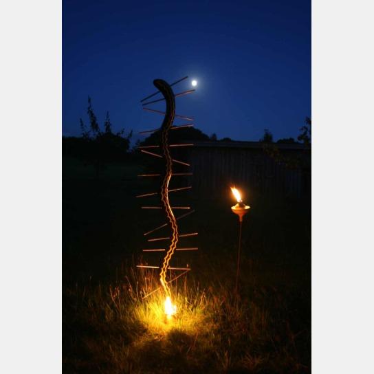 Eine Holzskulptur wird bei Dunkelheit von einer Fackel angeleuchtet.