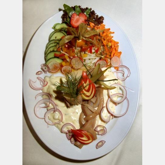 Leckere Matjesfilets als Zopfmuster auf Hausfrauensoße angerichtet, umgeben von frischen Zwiebelringen und einer Salatbeilage