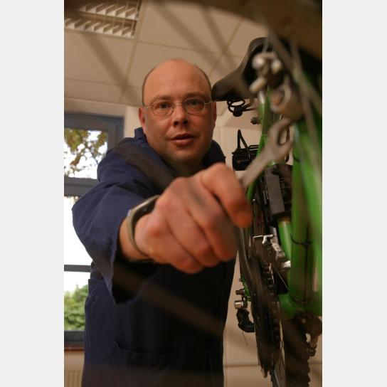Ein Mitarbeiter schraubt mit einem Schraubelschlüssel an einem Hinterrad