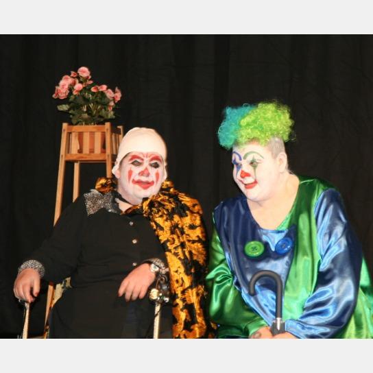 1 Clown mit zerzausten Haaren in Blau und Grün und ein Clowns in Schwarz mit Tigerumhang
