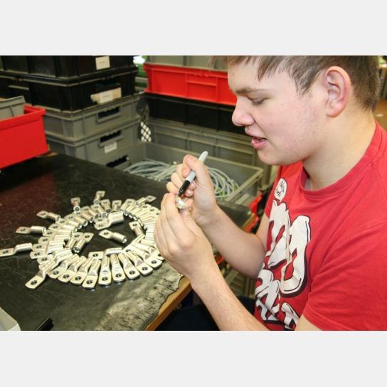 Bild Ein Mitarbeiter beschriftet Bauteile