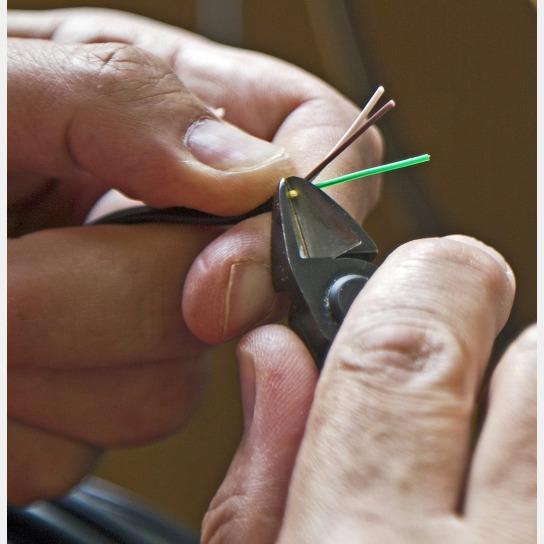 Bild Nahaufnahme von Händen, die ein Kabel mit ei