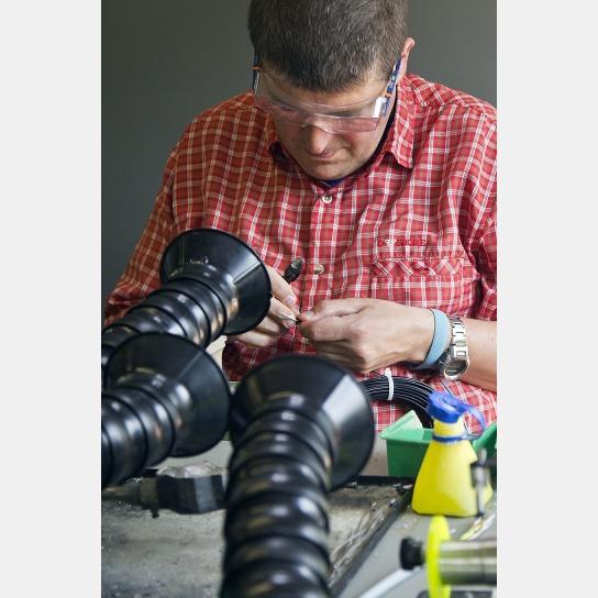 Bild Ein Mitarbeiter mit Handicap arbeitet am Arbeitsplatz für Lötarbeiten