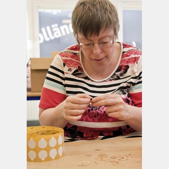 Bild Eine Mitarbeitende mit Handicap klebt Klebepu
