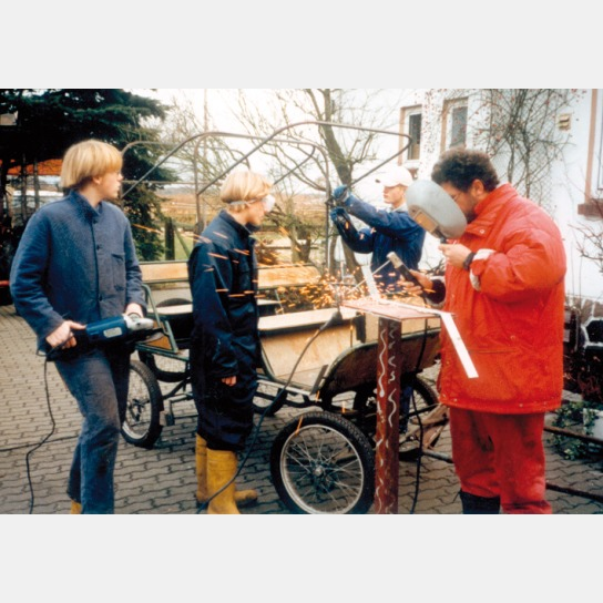 3 Jugendliche überholen unter fachkundiger Anleitung eine kutsche