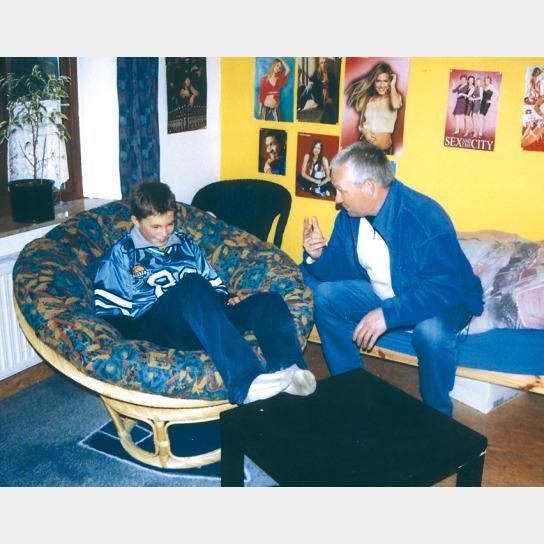 Jugendlicher sitzt im Sessel und liest einer männlichen Person etwas vor