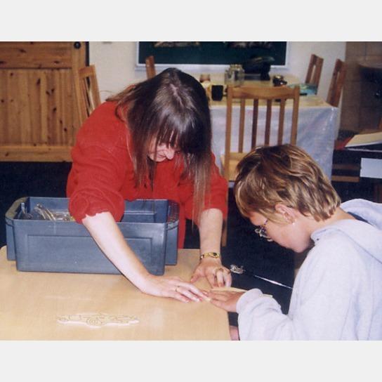 Betreuerin und Kind arbeiten mit einer Holzplatte