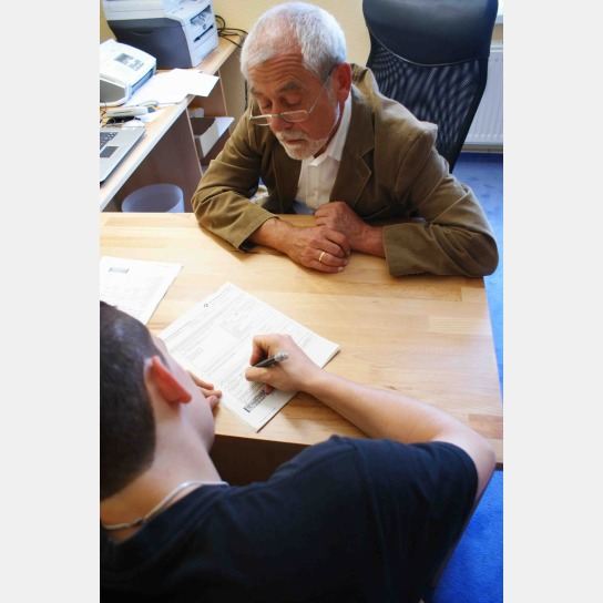 Betreuer beaufsichtigt Teenager bei Schreibarbeit auf einem Schreibtisch