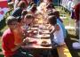 Alle Kinder essen gemeinsam auf dem Rasen vor der Pamir