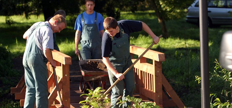 Vier Männer bei Landschaftsbauarbeiten