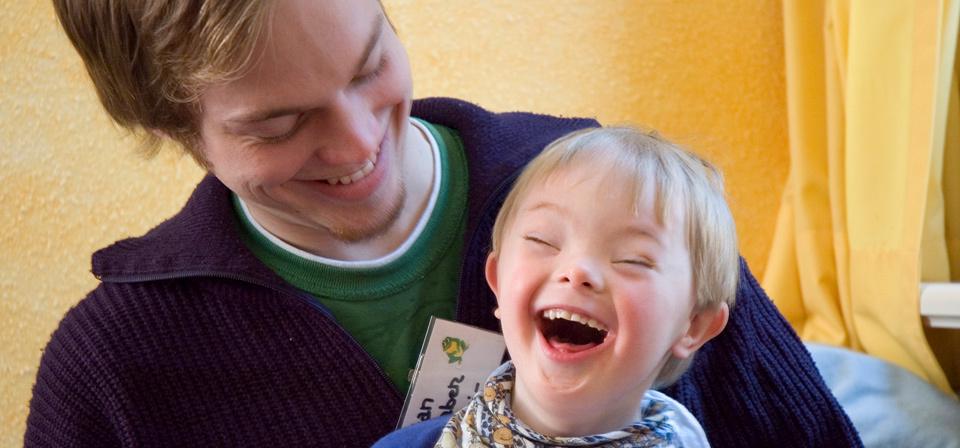Ein Erzieher lacht mit einem Kind aus der Kinderta